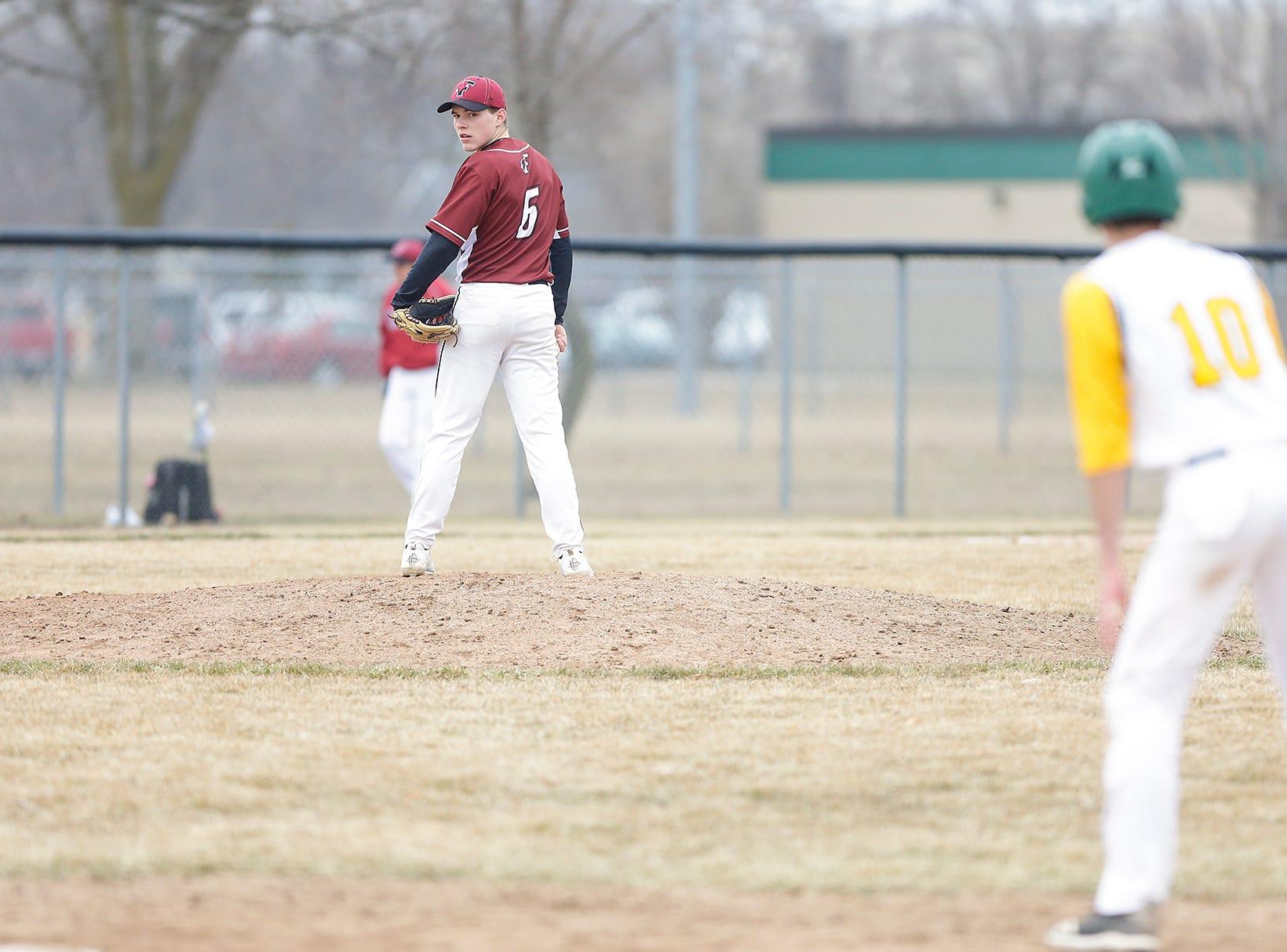 Fond du Lac High School baseball's Fletcher Haus checks on Ashwaubenon High School's Luke Hansford at first base Saturday, April 6, 2019 during their game in Fond du Lac, Wis. Fond du Lac won the game 5-3. Doug Raflik/USA TODAY NETWORK-Wisconsin