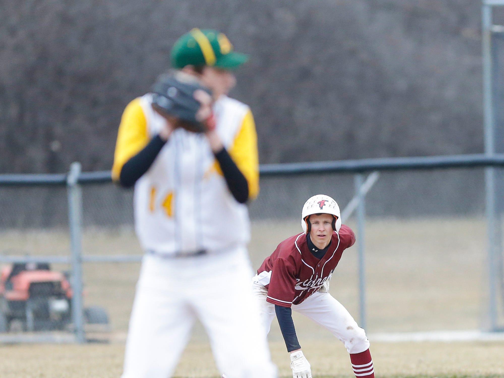 Fond du Lac High School baseball's Caden Krug keeps an eye on Ashwaubenon High School's Aaron Bliek as he leads off first base Saturday, April 6, 2019 during their game in Fond du Lac, Wis. Fond du Lac won the game 5-3. Doug Raflik/USA TODAY NETWORK-Wisconsin