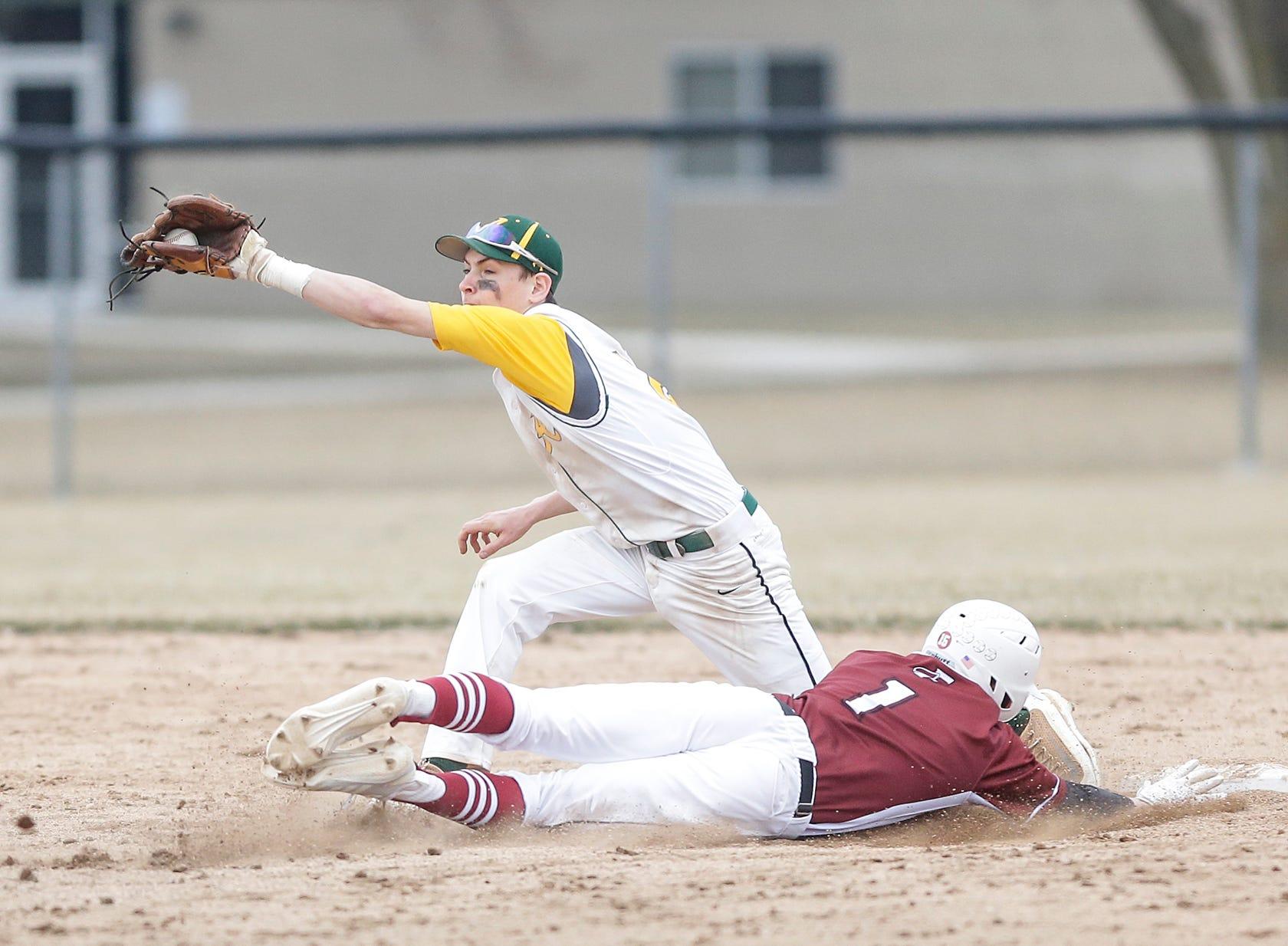 Fond du Lac High School baseball's Caden Krug (1) steals second base as Ashwaubenon High School's Ian MacLean (2) catches the ball Saturday, April 6, 2019 during their game in Fond du Lac, Wis. Fond du Lac won the game 5-3. Doug Raflik/USA TODAY NETWORK-Wisconsin