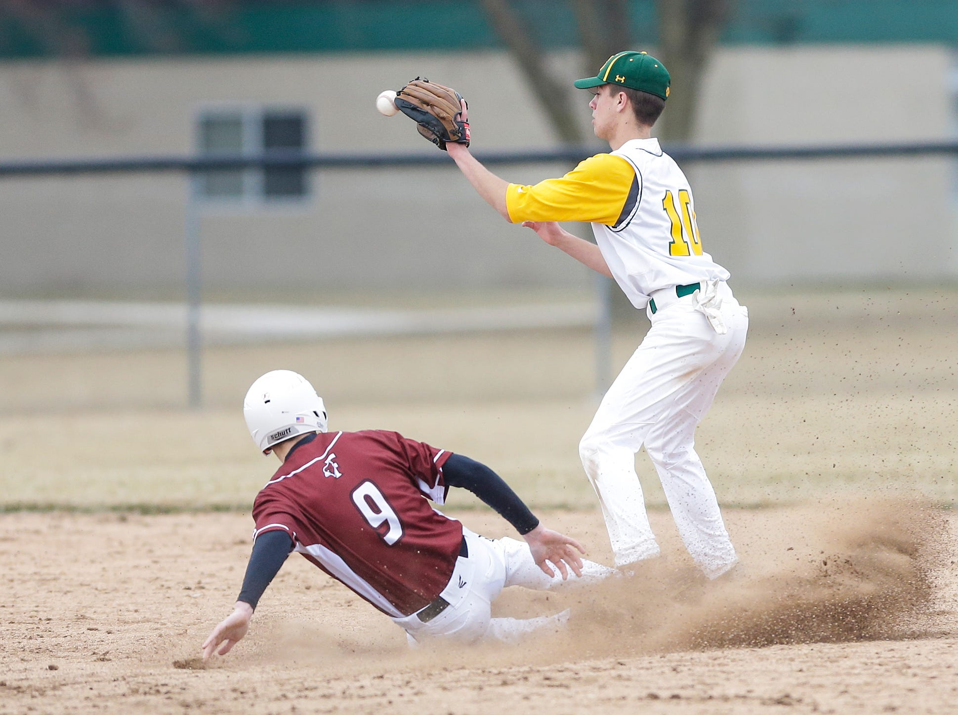 Fond du Lac High School baseball's Eli Schipper (9) gets tagged out at second base by Ashwaubenon High School's Luke Hansford (10) Saturday, April 6, 2019 during their game in Fond du Lac, Wis. Fond du Lac won the game 5-3. Doug Raflik/USA TODAY NETWORK-Wisconsin