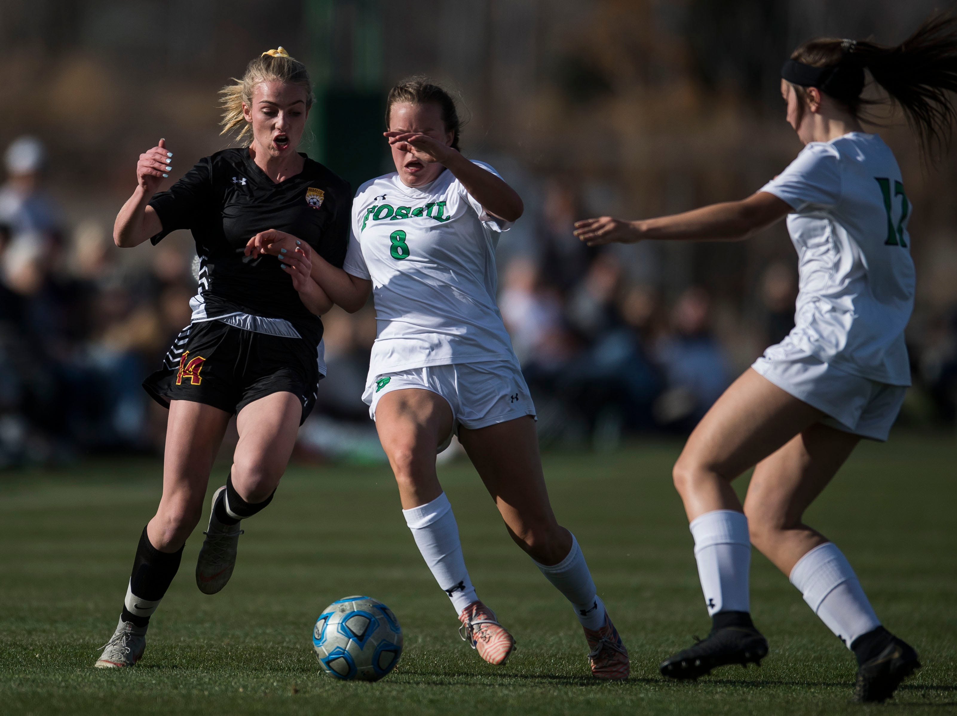 Rocky Mountain High School sophomore Mya Johnson (14) goes up against Fossil Ridge High School senior Jordyn Moser (8) and junior Brianna Punis (17) on Friday, April 4, 2019, at Colorado State University's soccer field in Fort Collins, Colo.