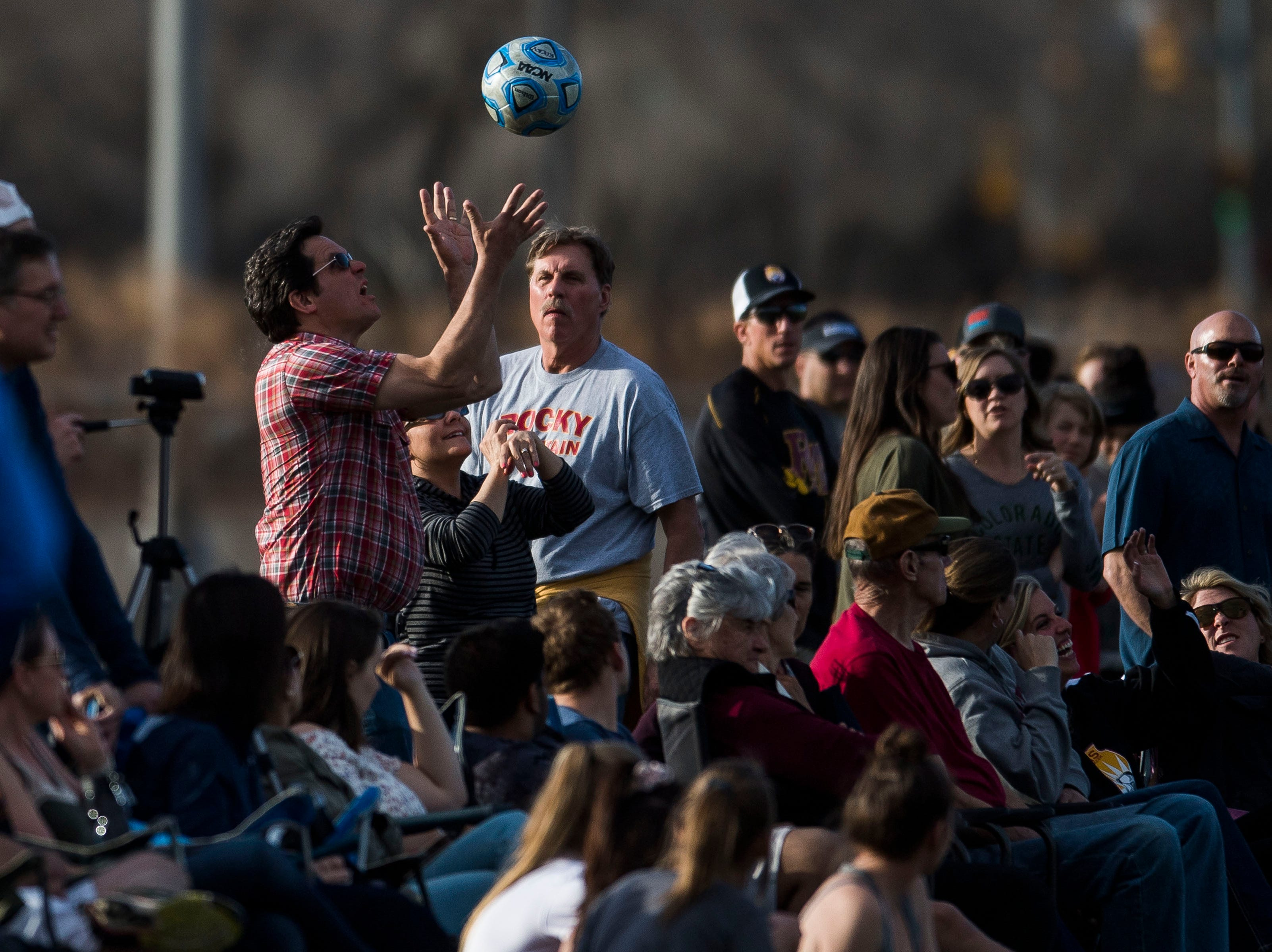 A fan catches an out-of-bounds ball during a game between Rocky Mountain High School and Fossil Ridge High School on Friday, April 4, 2019, at Colorado State University's soccer field in Fort Collins, Colo.