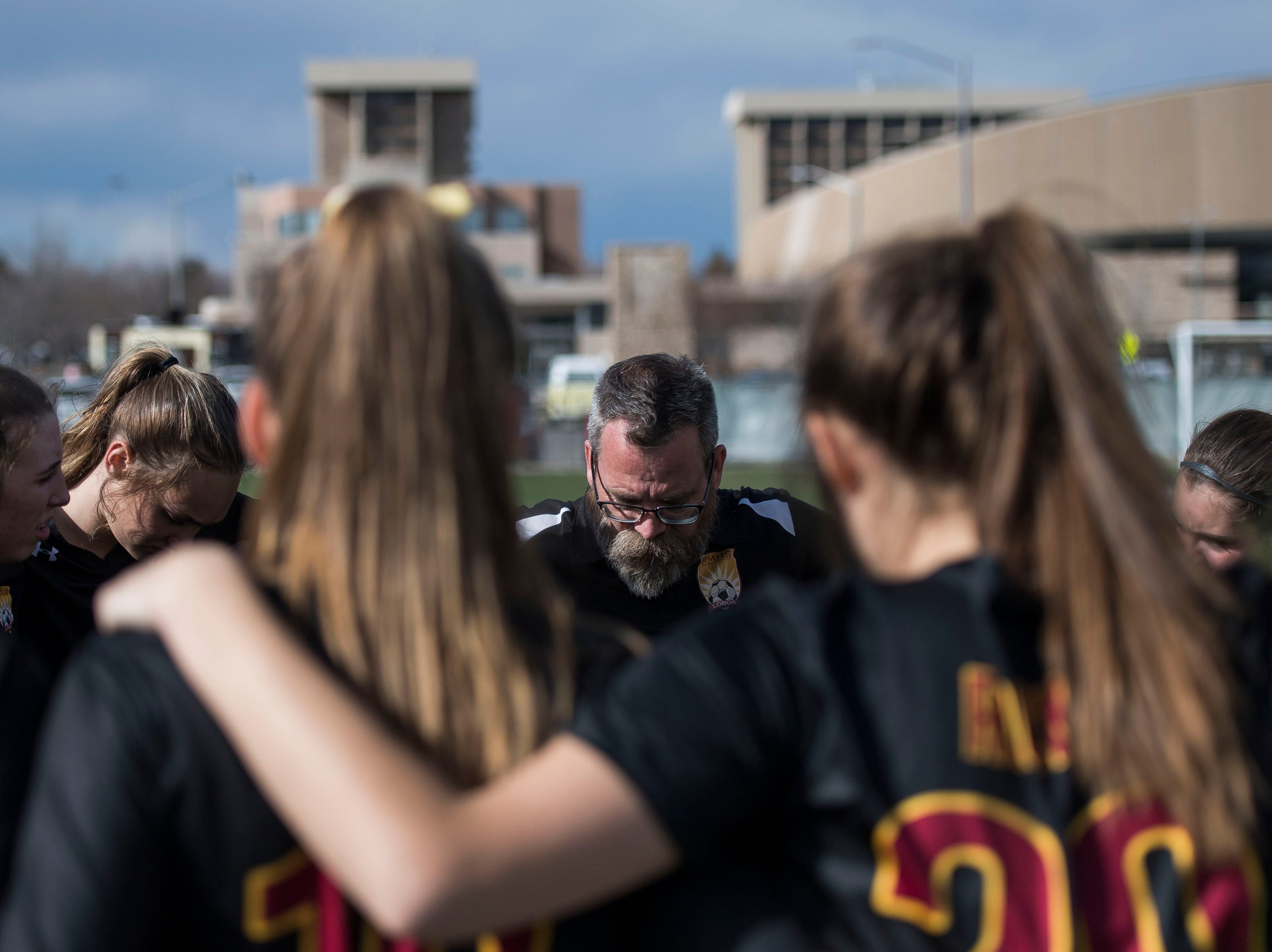 Rocky Mountain High School head coach Ron Clark huddles up with the team before a game against Fossil Ridge High School on Friday, April 4, 2019, at Colorado State University's soccer field in Fort Collins, Colo.