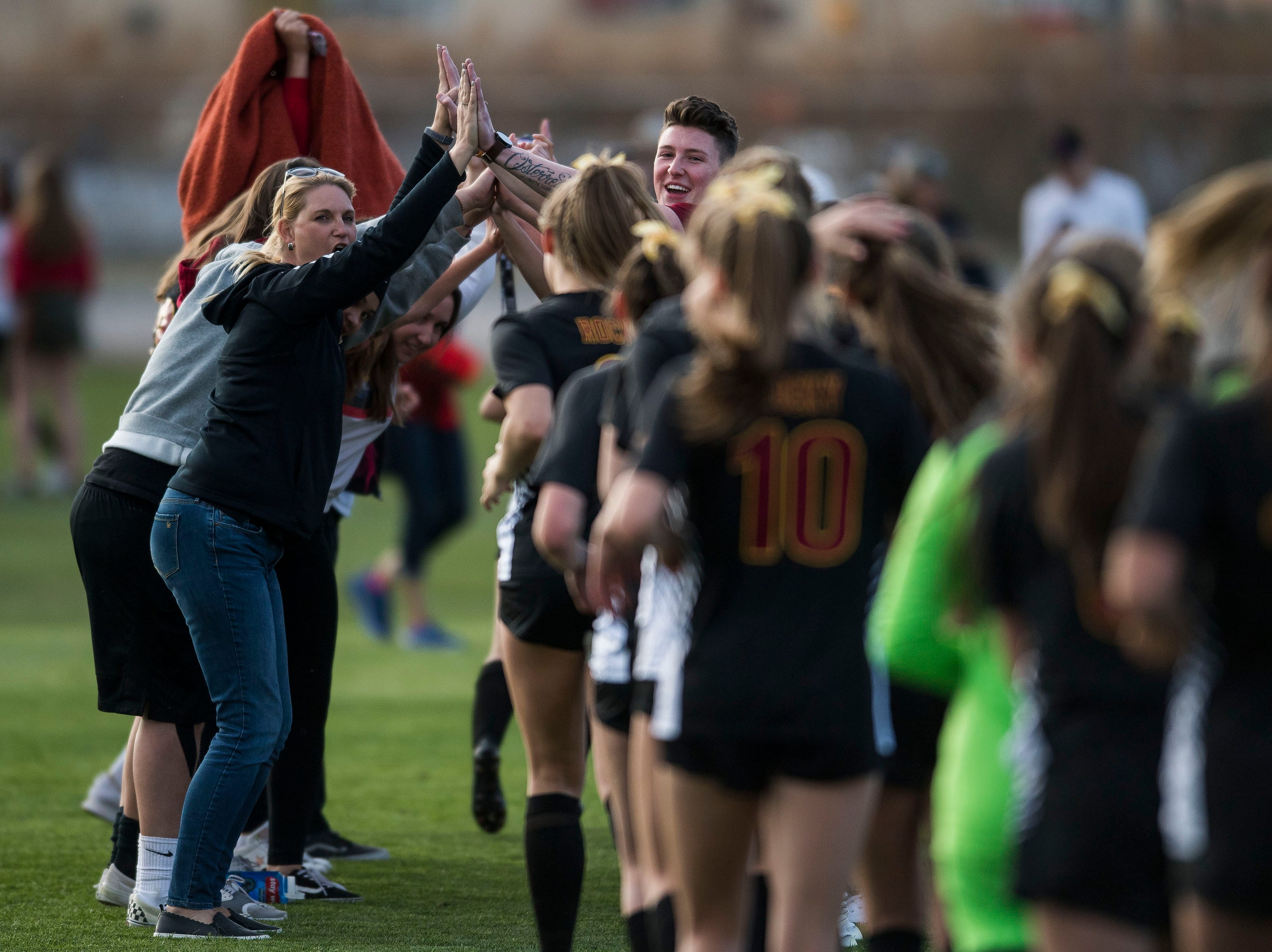 Rocky Mountain High School fans create a tunnel for the team to run through after a 2-0 win over Fossil Ridge High School on Friday, April 4, 2019, at Colorado State University's soccer field in Fort Collins, Colo.
