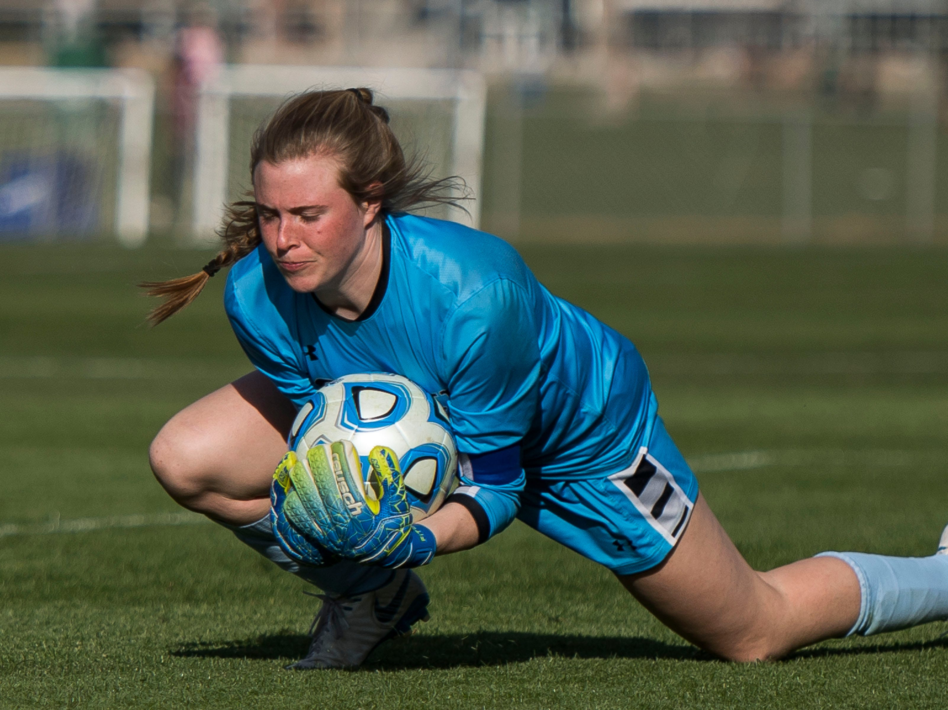 Fossil Ridge High School goalkeeper Emily Vangundy (1) dives on the ball during a game against Rocky Mountain High School on Friday, April 4, 2019, at Colorado State University's soccer field in Fort Collins, Colo.
