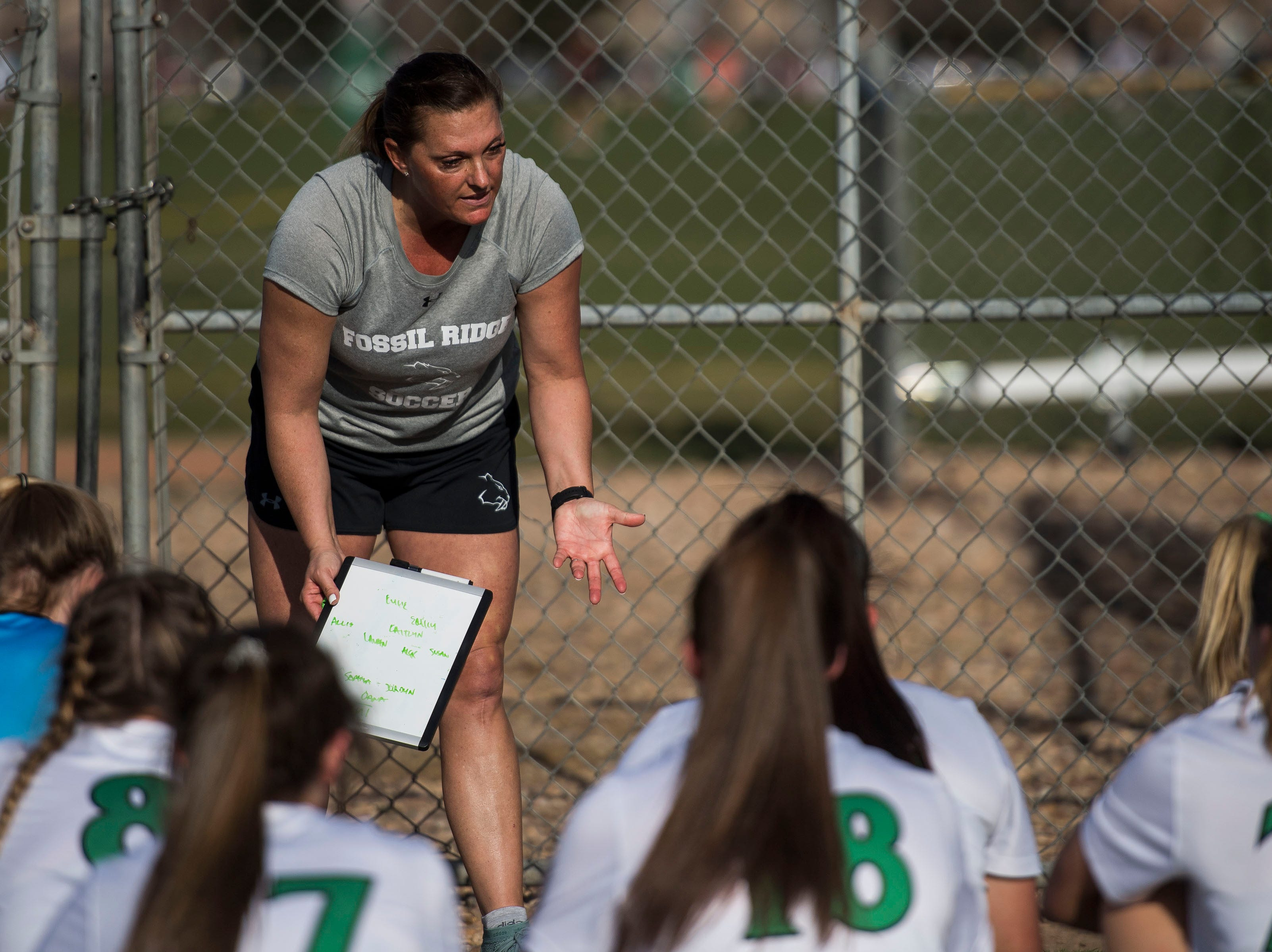 Fossil Ridge High School head coach Kim Whisenant talks with the team at halftime during a game against Rocky Mountain High School on Friday, April 4, 2019, at Colorado State University's soccer field in Fort Collins, Colo.