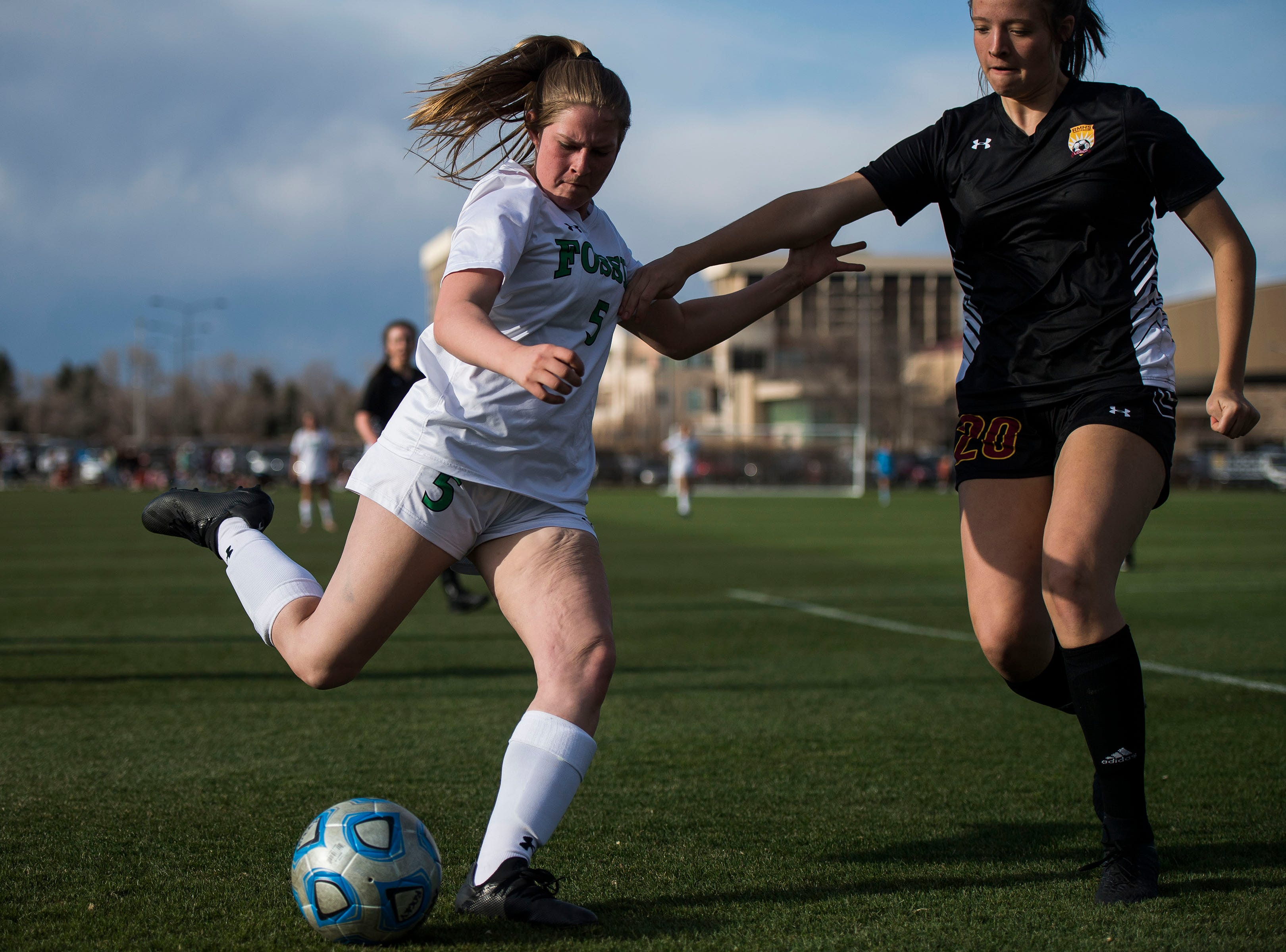 Fossil Ridge High School junior Kylie Harger (5) attempts to shoot on goal past Rocky Mountain High School sophomore Sydney Romero (20) on Friday, April 4, 2019, at Colorado State University's soccer field in Fort Collins, Colo.