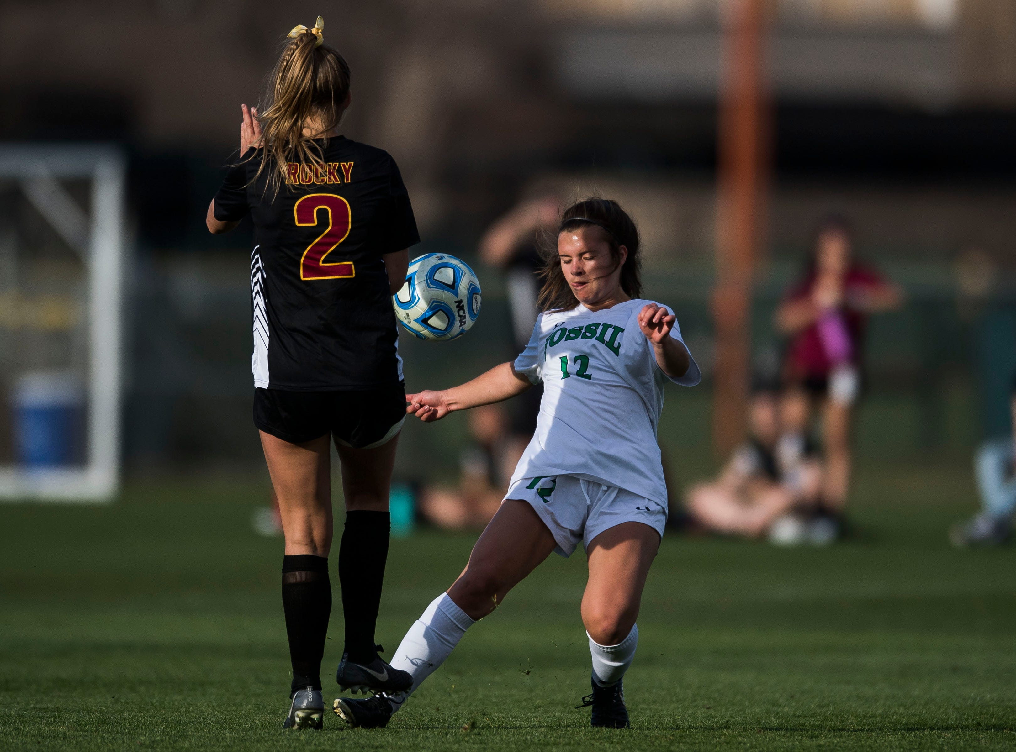 Fossil Ridge High School sophomore Kaitlyn Rogers (12) kicks a ball past Rocky Mountain High School senior Regan Ostler (2) on Friday, April 4, 2019, at Colorado State University's soccer field in Fort Collins, Colo.