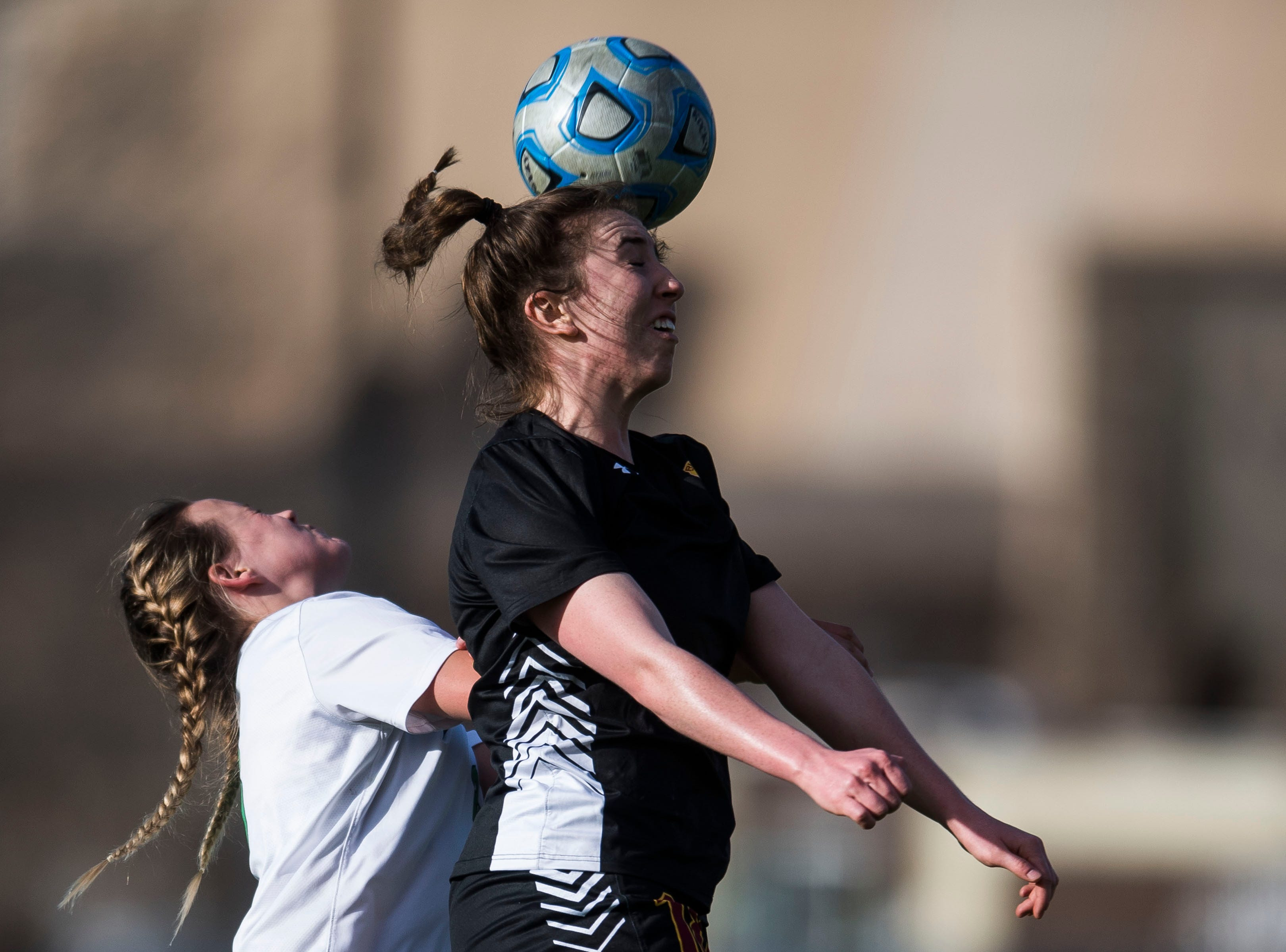 Rocky Mountain High School senior Mikayla Eccher (18) heads the ball over Fossil Ridge High School senior Jordyn Moser (8) on Friday, April 4, 2019, at Colorado State University's soccer field in Fort Collins, Colo.