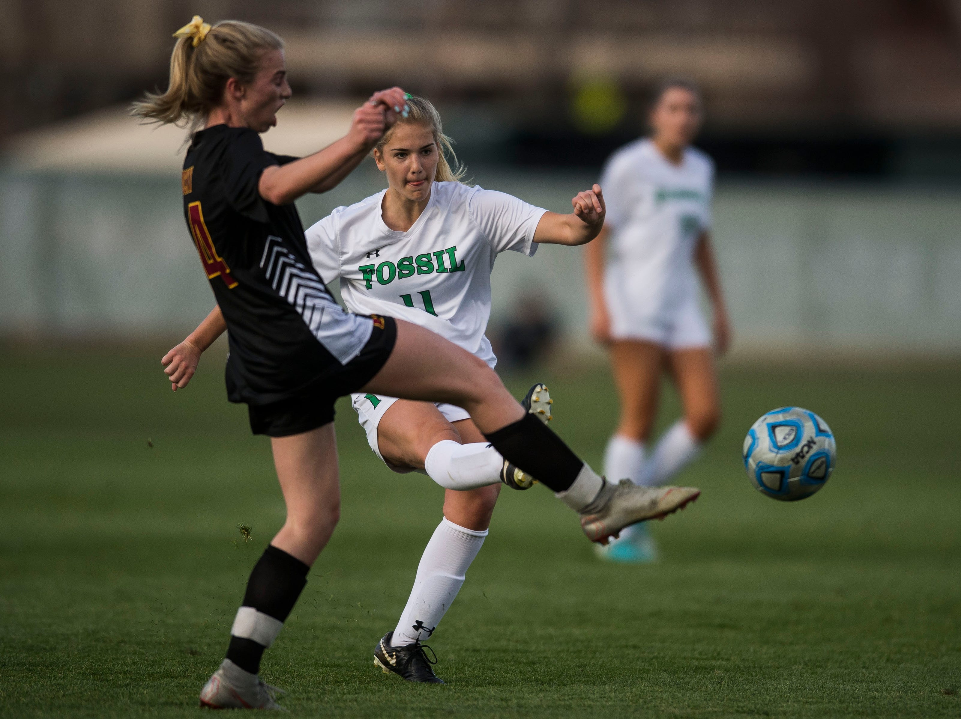 Fossil Ridge High School senior Emily Drysdale (11) kicks past Rocky Mountain High School sophomore Mya Johnson (14) on Friday, April 4, 2019, at Colorado State University's soccer field in Fort Collins, Colo.