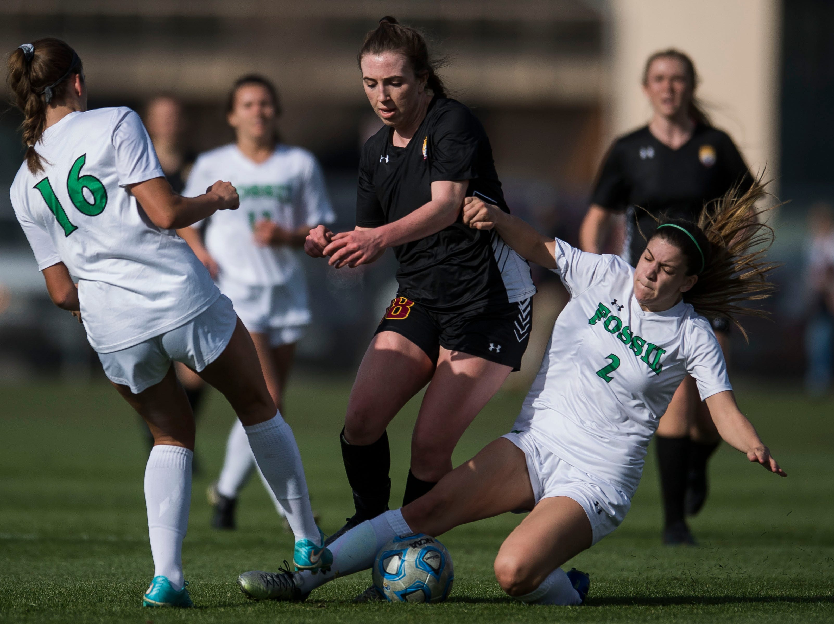 Rocky Mountain High School senior Mikayla Eccher (18) gets tangles up with Fossil Ridge High School senior Alex Lockwood (2) and senior Lauren Martis (16) on Friday, April 4, 2019, at Colorado State University's soccer field in Fort Collins, Colo.