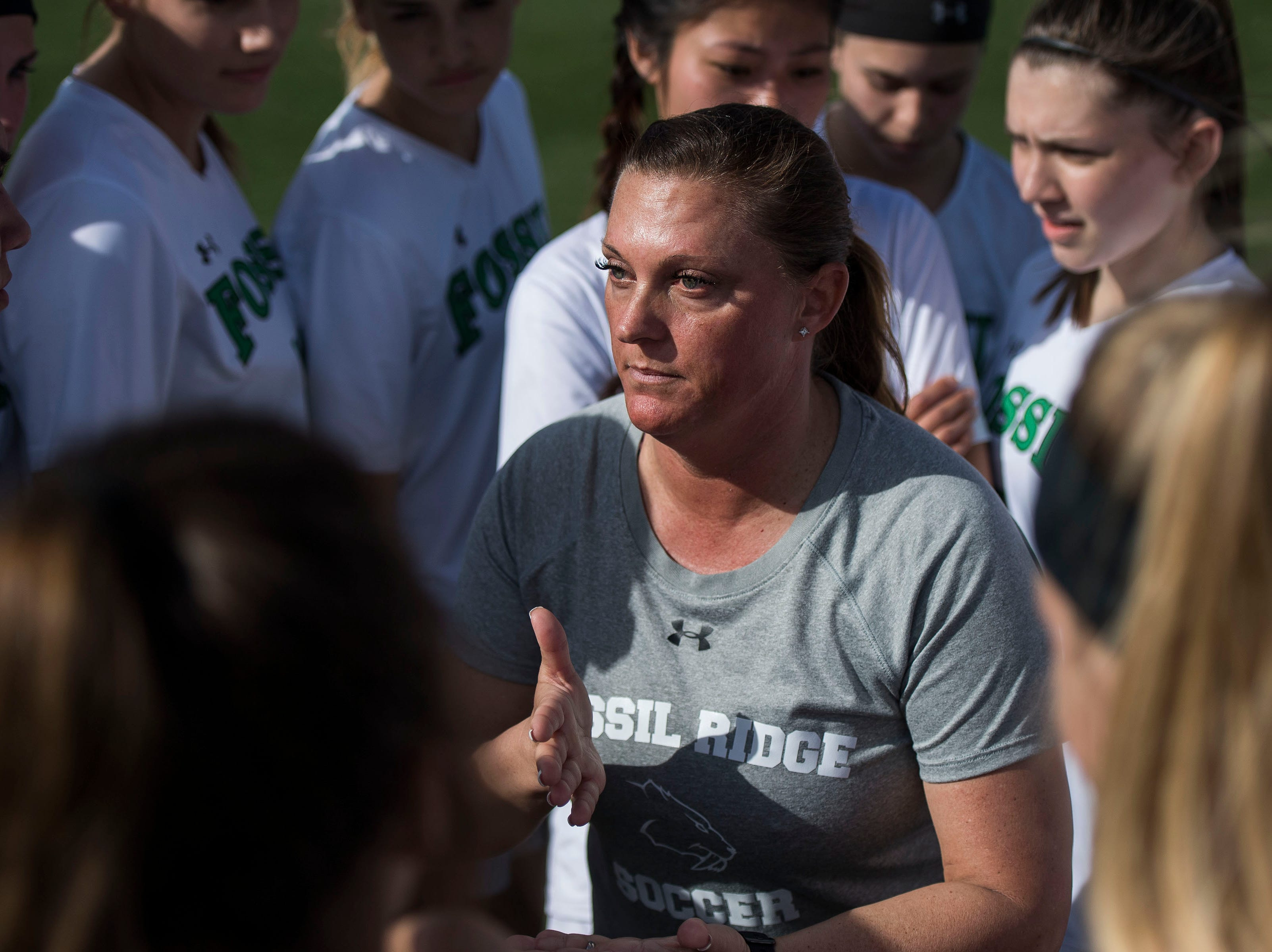 Fossil Ridge High School head coach Kim Whisenant huddles up wit tithe team before a game against Rocky Mountain High School on Friday, April 4, 2019, at Colorado State University's soccer field in Fort Collins, Colo.