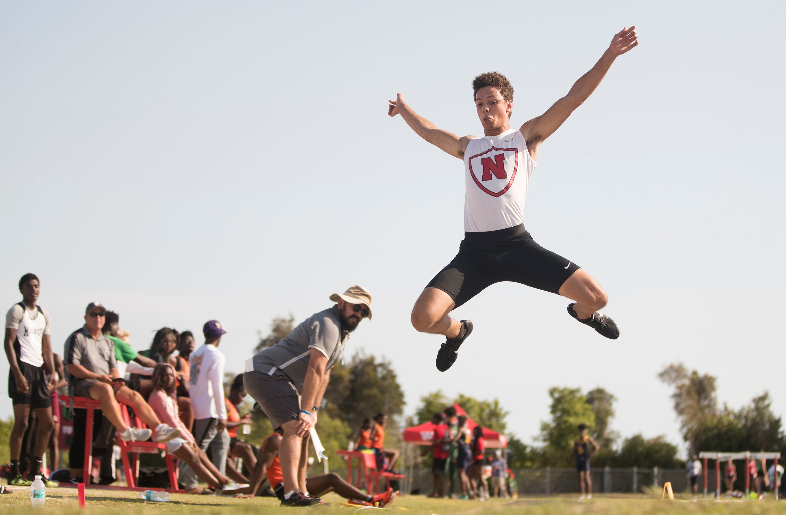 North Fort Myers High School's Michael Johnson Sr. competes in the boys long jump on Friday during the Lee County Athletic Conference track and field championships at South Fort Myers. Johnson won the event.
