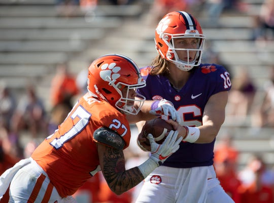Clemson quarterback Trevor Lawrence (16) hands the ball to running back Ty Lucas (27) during the spring game at Memorial Stadium Saturday, April 6, 2019.
