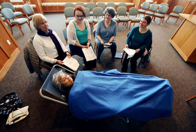 Choir member Anna Dockter reclines in a chair as other members of Montana's only Threshold Choir chapter sing to her during their weekly practice at Big Sky Senior Living in Butte, Mont. (Meagan Thompson/Montana Standard via AP)