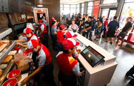 Food orders are prepared of some of the hundreds of eager diners who waited for the opening of the Jollibee restaurant at the Micronesia Mall in Dededo on Saturday, April 6, 2019.