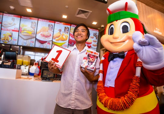 Landon Laureano, 15, the first customer to be served at the opening of the Jollibee restaurant at the Micronesia Mall is photographed with the fast food chain's mascot in Dededo on Saturday, April 6, 2019. Laureano said he showed up at 9:00 p.m., Friday evening, to start the line for the opening of the popular Filipino fast food chain. Despite not having eaten at Jollibee before, Laureano said that Chickenjoy and Yumburger were at the top of his list when he places his order.
