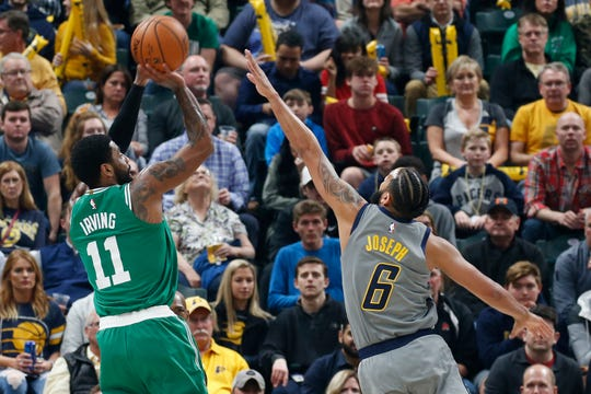 Boston Celtics guard Kyrie Irving (11) takes a shot against Indiana Pacers guard Cory Joseph (6) during the first quarter at Bankers Life Fieldhouse.