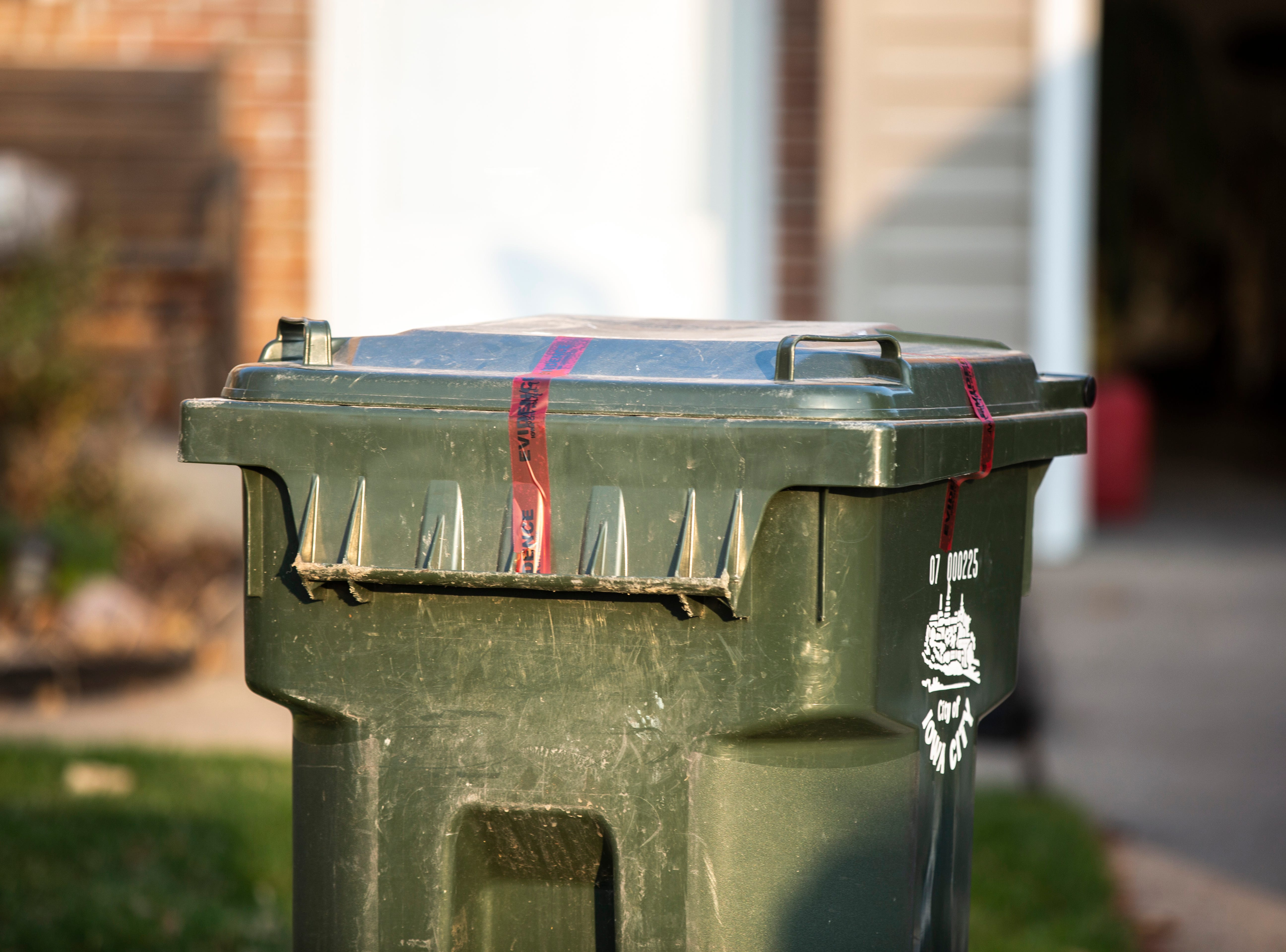 A garbage can is sealed with evidence tape while police investigators respond to a scene of a suspicious death on Friday, April 5, 2019, at 114 Green Mountain Drive in Iowa City, Iowa.