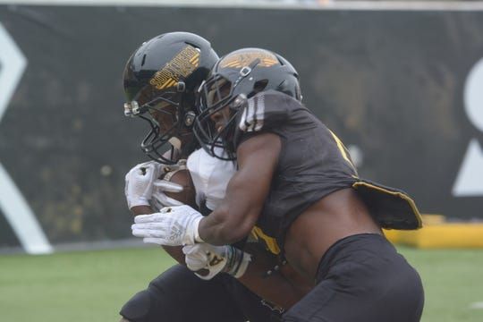Southern Miss wide receiver Raymond Smith Jr. collides with a USM defensive back Saturday, April 6, during a drill.