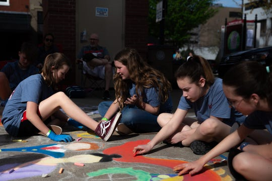 Kinsey Gentry,13, left, and Lauren Hill, 12, center, both students of West Valley middle school collaborate on a drawing with their classemates during the Dogwood Arts annual Chalk Walk in Market Square Saturday, April 6, 2019.