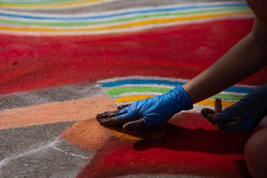 A young artist blends their work during the Dogwood Arts annual Chalk Walk in Market Square Saturday, April 6, 2019.