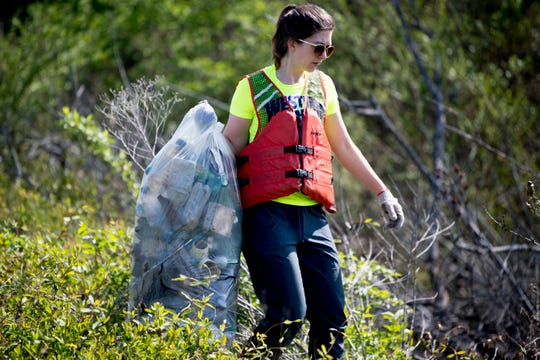 Kristina Breidenstein carries a bag full of collected trash during a river clean up of the Clinch River near Solway Park in Oak Ridge, Tennessee on Saturday, April 6, 2019. Dozens of volunteers cleaned up several areas on the river of debris and trash.