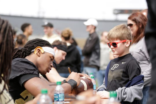 Purdue running back Alfred Armour (22) signs an autograph for Corbin Cox, 8, after the Purdue University spring game, Saturday, April 6, 2019, at Ross-Ade Stadium in West Lafayette. The defense won, 53-39, using a modified scoring system.