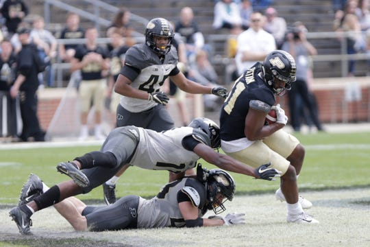 Purdue tight end Darius Pittman (81) attempts to dodge Purdue defensive back Kadin Smith (11), center, after a missed tackle by Purdue linebacker Byron Hubbard (45), bottom, during the fourth quarter of the Purdue University spring game, Saturday, April 6, 2019, at Ross-Ade Stadium in West Lafayette.(Nikos Frazier | The Journal & Courier)