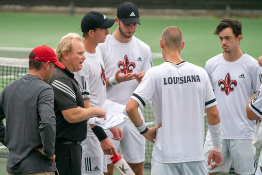 UL men's tennis coach Mark Jeffrey talks to his players on the court April 5, as the Ragin' Cajuns take on South Alabama at Cajun Courts.