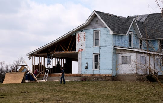Volunteers work to repair the damage from last month's tornado to the Bruff home in Shiawassee County Saturday, April 6, 2019.