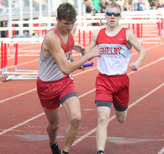 Shelby's Blake Lucius receives a handoff from teammate Sam Swanger during the boys 4x800 relay race at last Saturday's Shelby Invitational. Those two joined Caleb Brown and Sam Logan to win an indoor state championship this year.