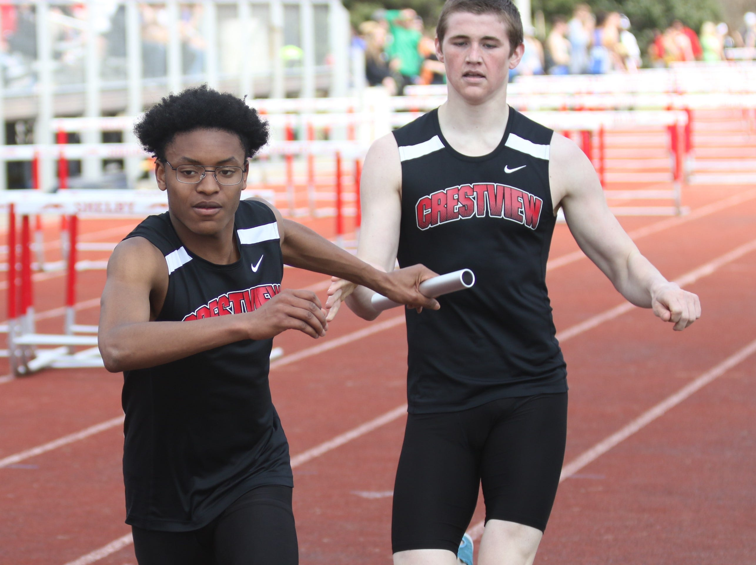 Crestview's James Barber receives the hand off from teammate Ross Kuhn for the championship 4x800 team during the Shelby High School Invitational on Saturday afternoon.