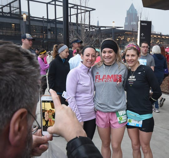 Jill Burroughs of Bloomington, Ill., (from left), Brie HInes of Chicago and Cheryl Richards of  Bloomington, Ill., have their picture taken in front of Fiserv Forum before the start of the Milwaukee Marathon on Saturday, April 6, 2019.