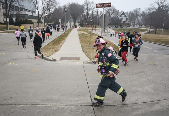 A runner in full firefighter gear makes the turn from East Water Tower Drive to North Terrace Avenue during the Milwaukee Marathon on Saturday, April 6, 2019.
