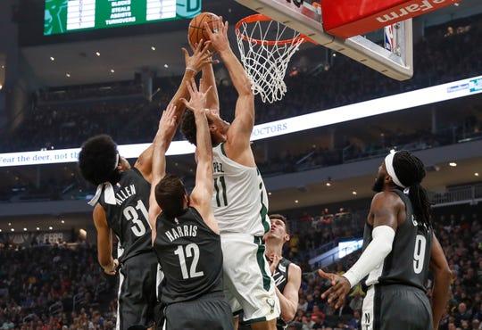 Bucks center Brook Lopez gets off a shot despite the defense of the Nets' Jarrett Allen and Joe Harris.