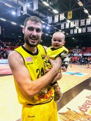 Chase Fieler with his son, Daxton, while playing in Belgium.