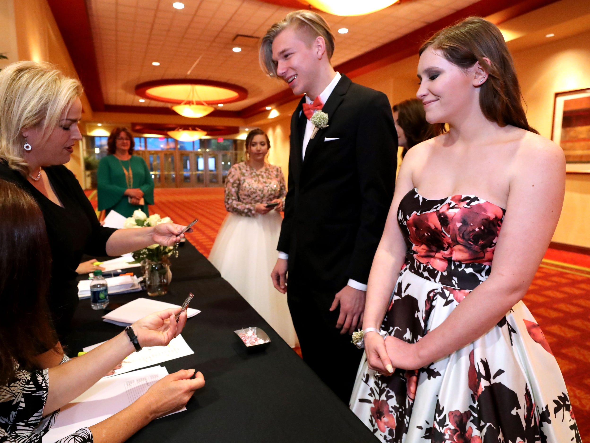 Jadyn Fox and Natalie Taylor check in at Eagleville's  Prom held at Embassy Suites, in Murfreesboro on Thursday April 5, 2019.