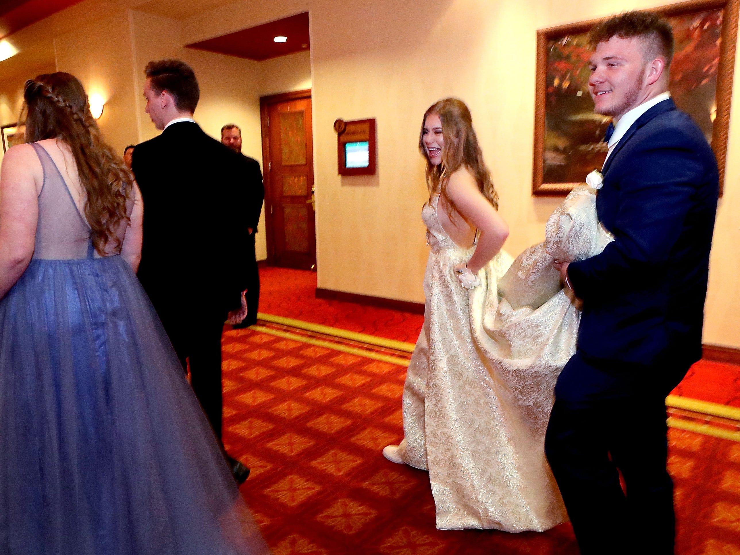 Carl Gudvangen holds Hannah Batt's dress off the ground as she walks into Eagleville's Prom held at Embassy Suites, in Murfreesboro on Thursday April 5, 2019.