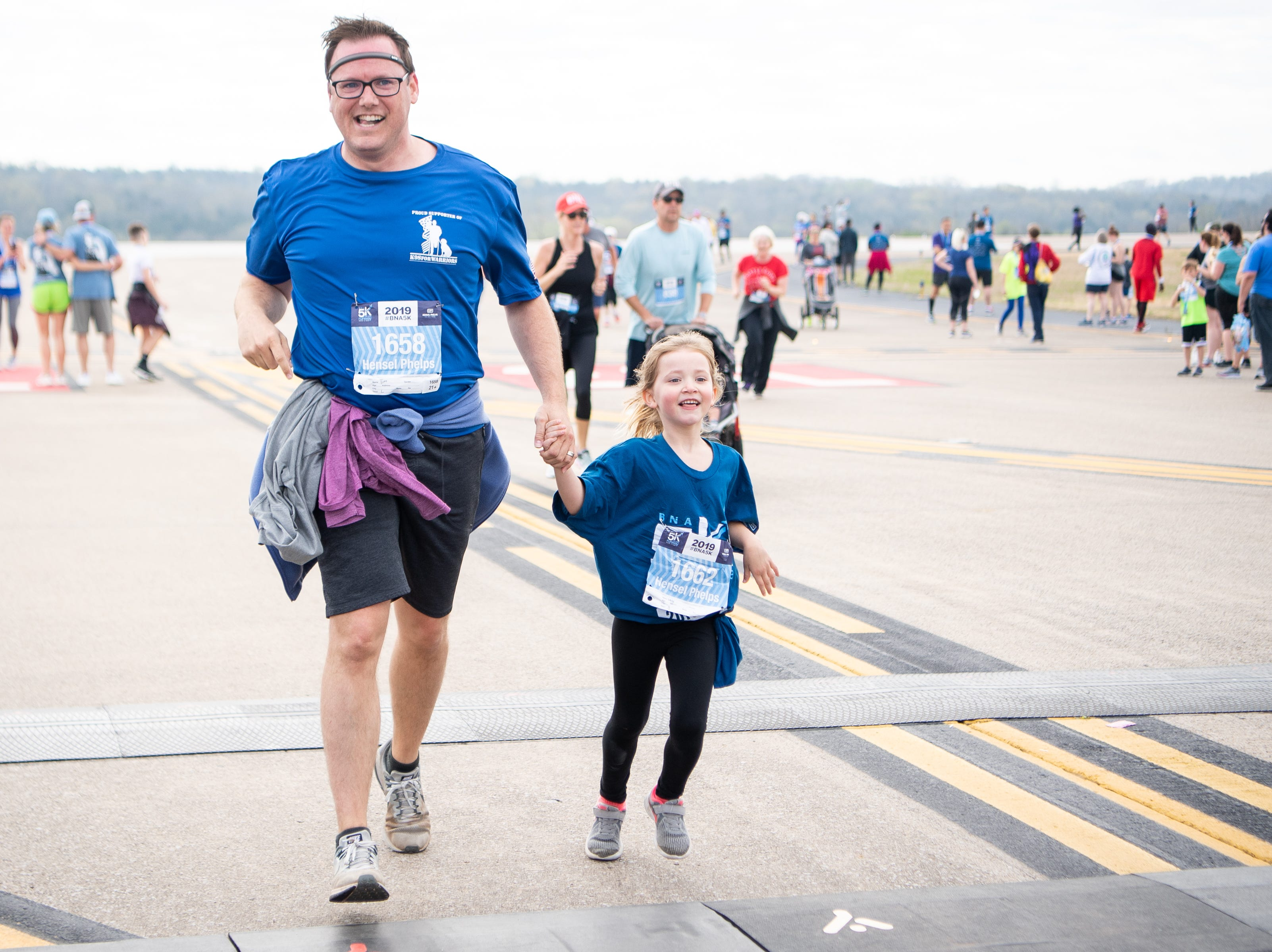 Lucy Davis, 5, runs across the finish line with her father, Tim Davis, during the BNA 5K on the Runway at Nashville International Airport on Runway 2R/20L Saturday, April 6, 2019, in Nashville, Tenn.