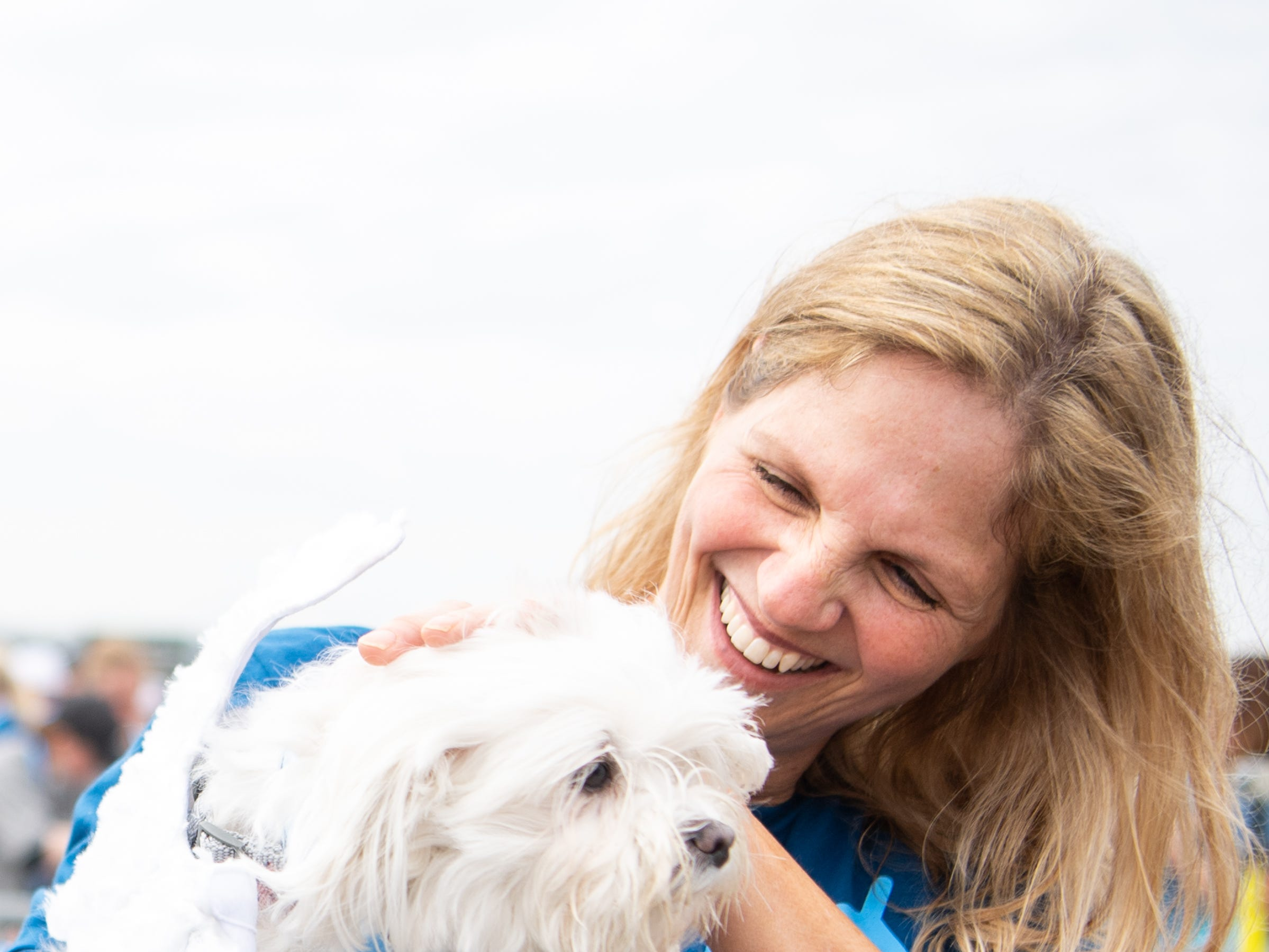 Candice Britain holds Luna after passing down her metal during the BNA 5K on the Runway at Nashville International Airport on Runway 2R/20L Saturday, April 6, 2019, in Nashville, Tenn.
