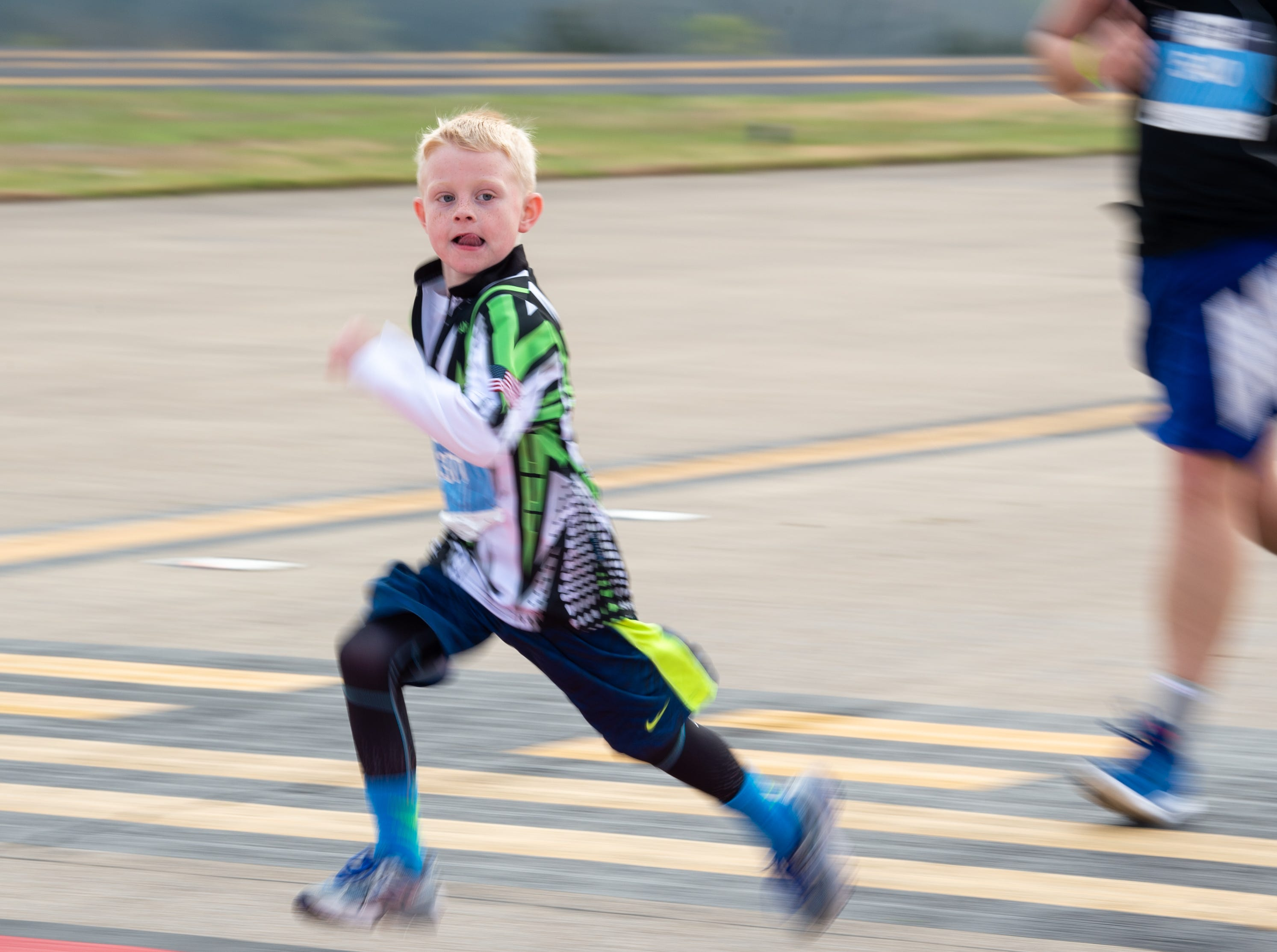 A child runs to the finish line during the BNA 5K on the Runway at Nashville International Airport on Runway 2R/20L Saturday, April 6, 2019, in Nashville, Tenn.