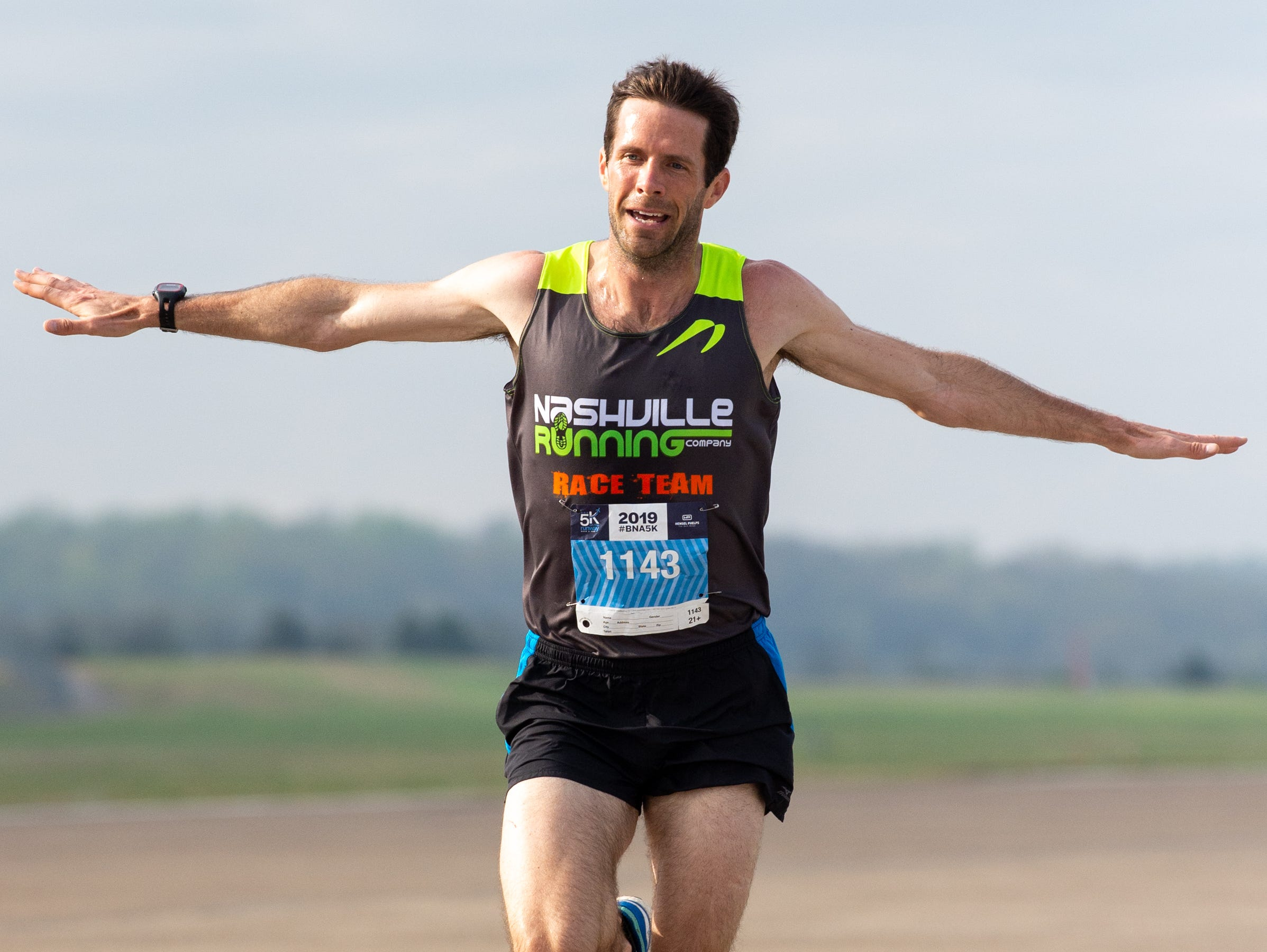 Ryan Snellen spreads out his arms like a plane before finishing the BNA 5K on the Runway first at Nashville International Airport on Runway 2R/20L Saturday, April 6, 2019, in Nashville, Tenn.