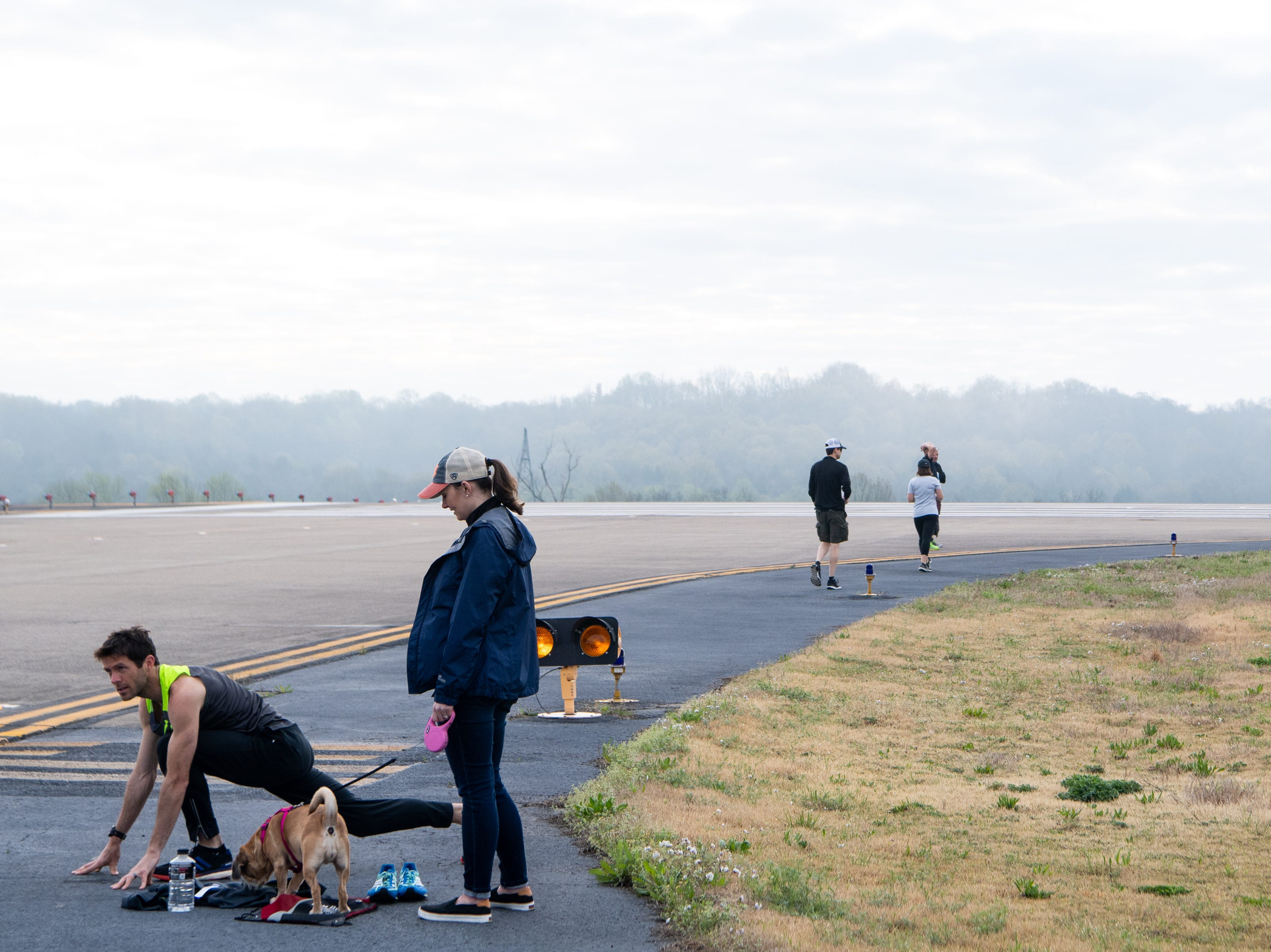 Ryan Snellen warms up with support from Brittany Snellen and their dog, Render, during the BNA 5K on the Runway at Nashville International Airport on Runway 2R/20L Saturday, April 6, 2019, in Nashville, Tenn.