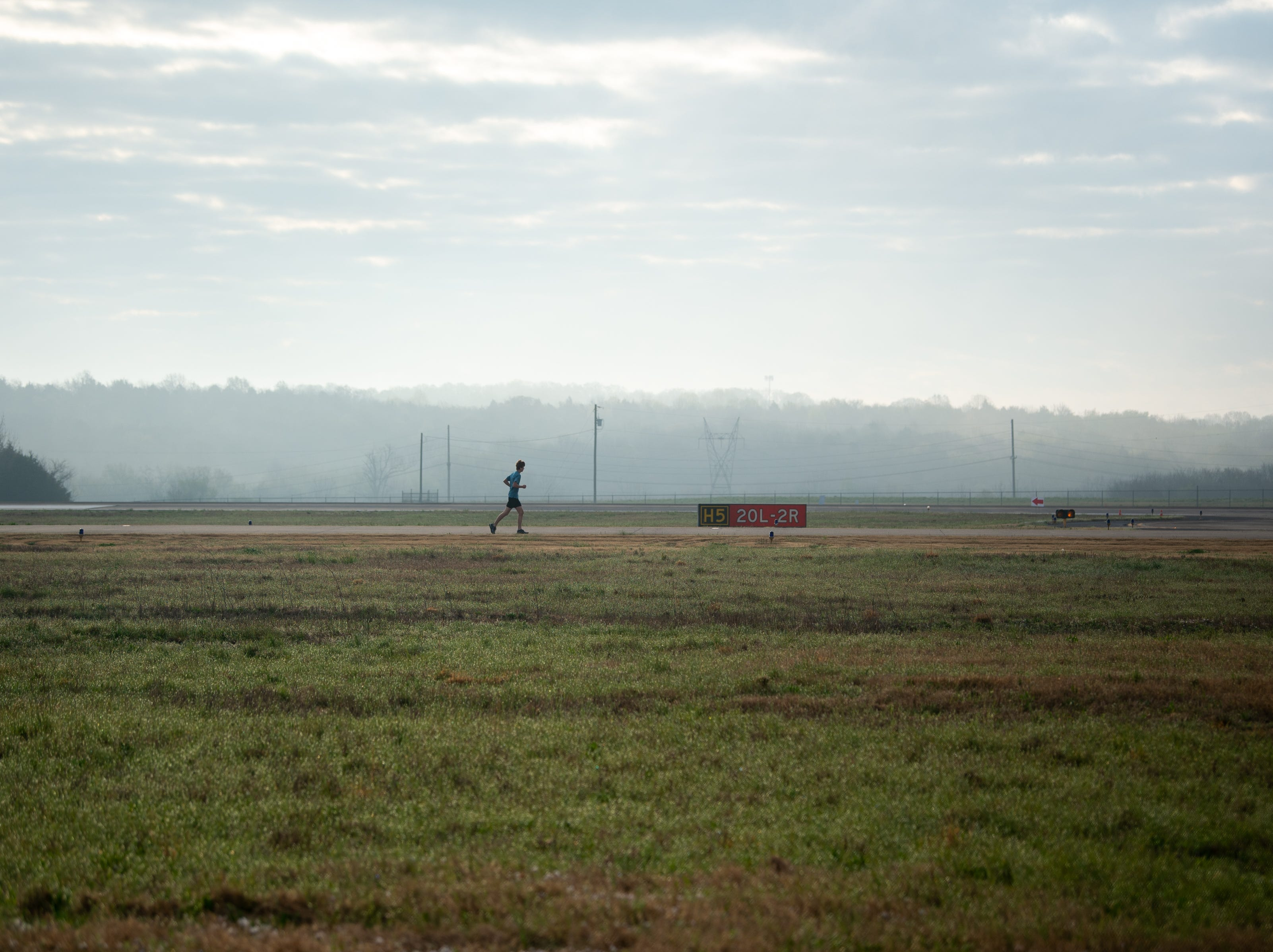 A runner warms up before the BNA 5K on the Runway at Nashville International Airport on Runway 2R/20L Saturday, April 6, 2019, in Nashville, Tenn.