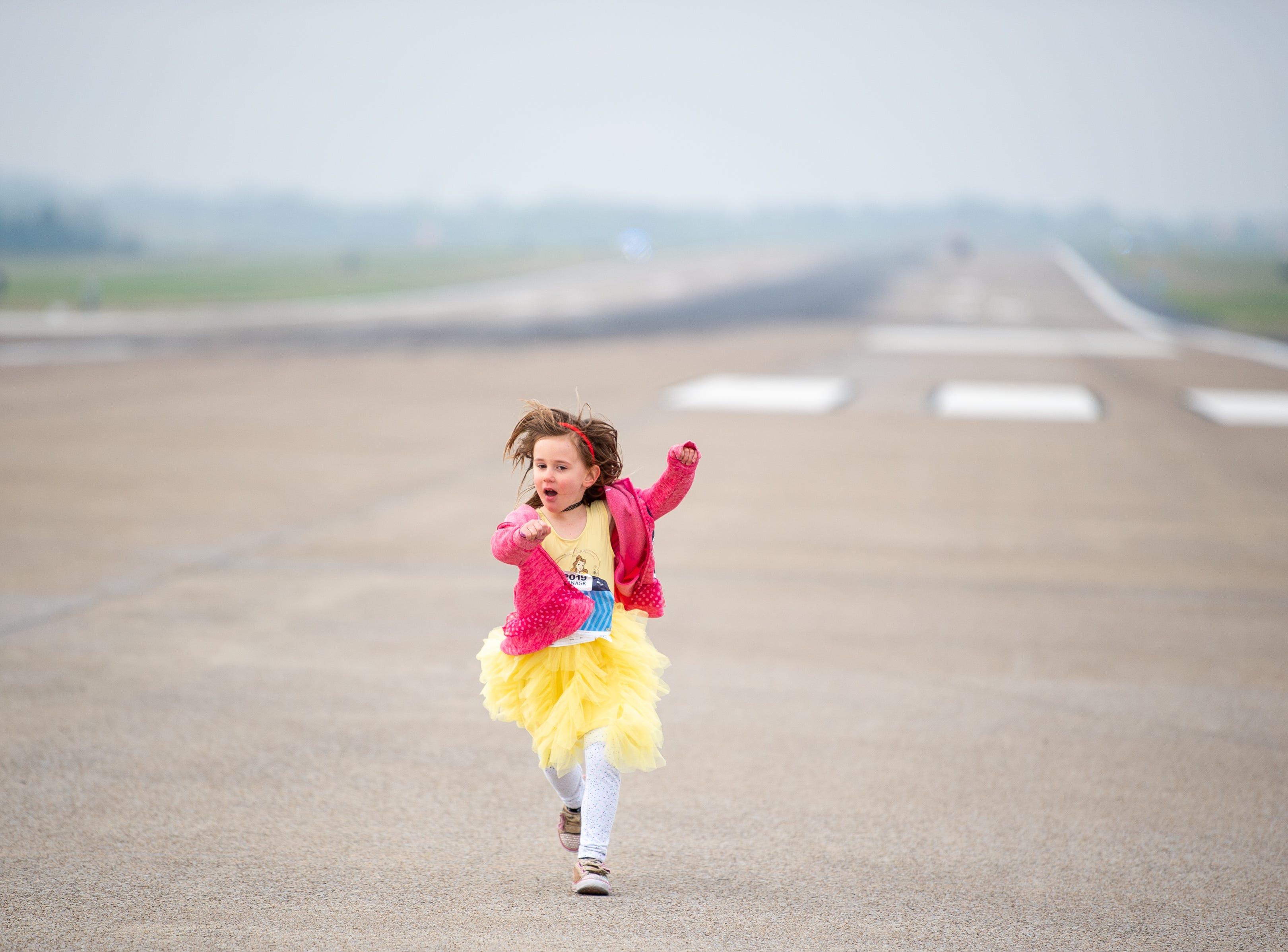 Ella Sward, 4, runs down Runway 2R/20L before the BNA 5K on the Runway at Nashville International Airport on Saturday, April 6, 2019, in Nashville, Tenn.