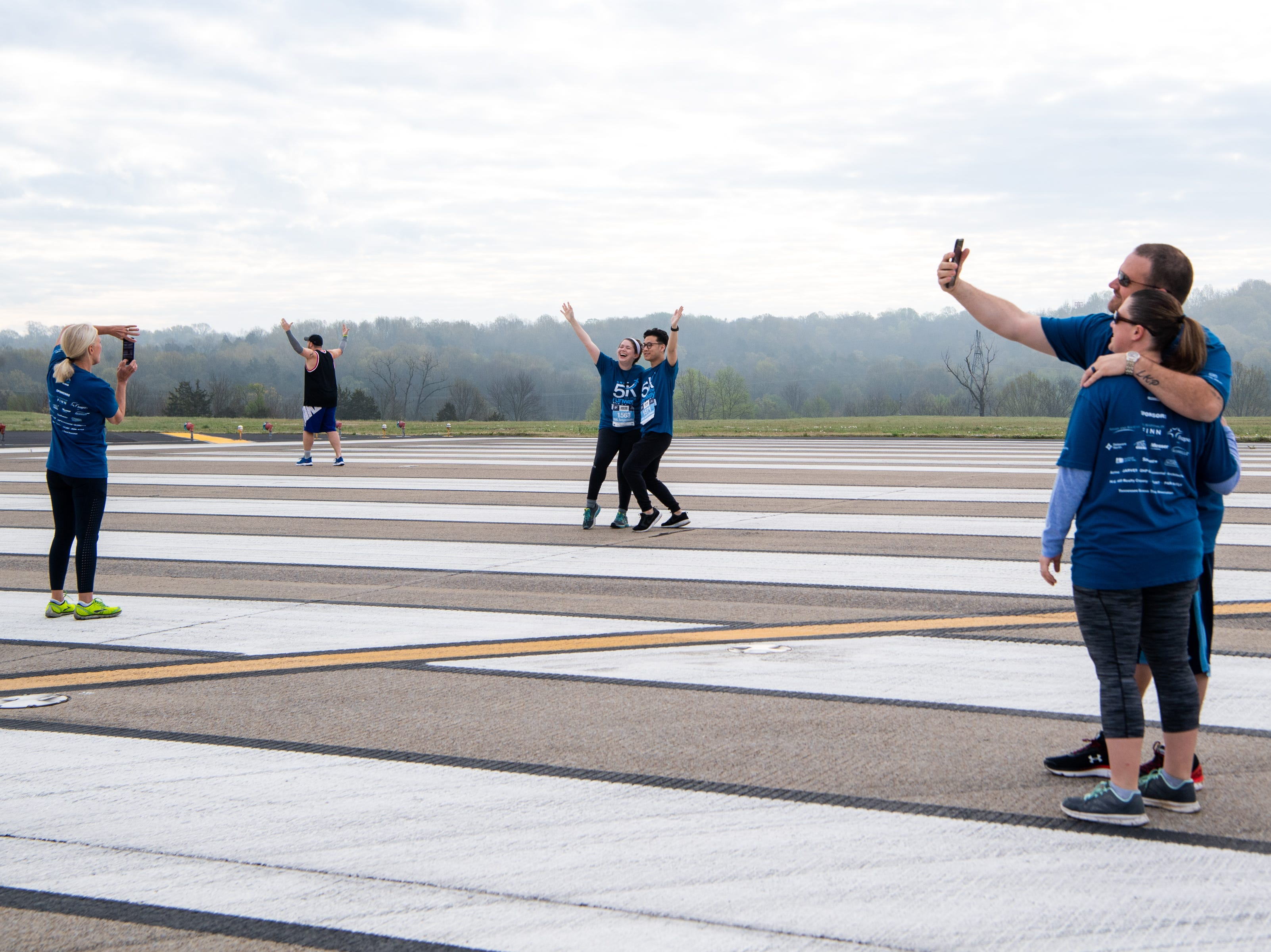 People take photos on Runway 2R/20L before the BNA 5K on the Runway at Nashville International Airport Saturday, April 6, 2019, in Nashville, Tenn.
