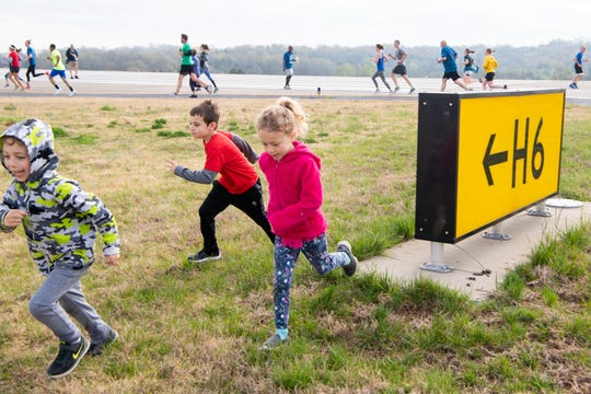 Riley Owens, 5, Brycen Loving, 7, and Addison Owens, 5, (from left) play near the taxiway intersection sign during the BNA 5K on the Runway at Nashville International Airport on Runway 2R/20L Saturday, April 6, 2019, in Nashville, Tenn.