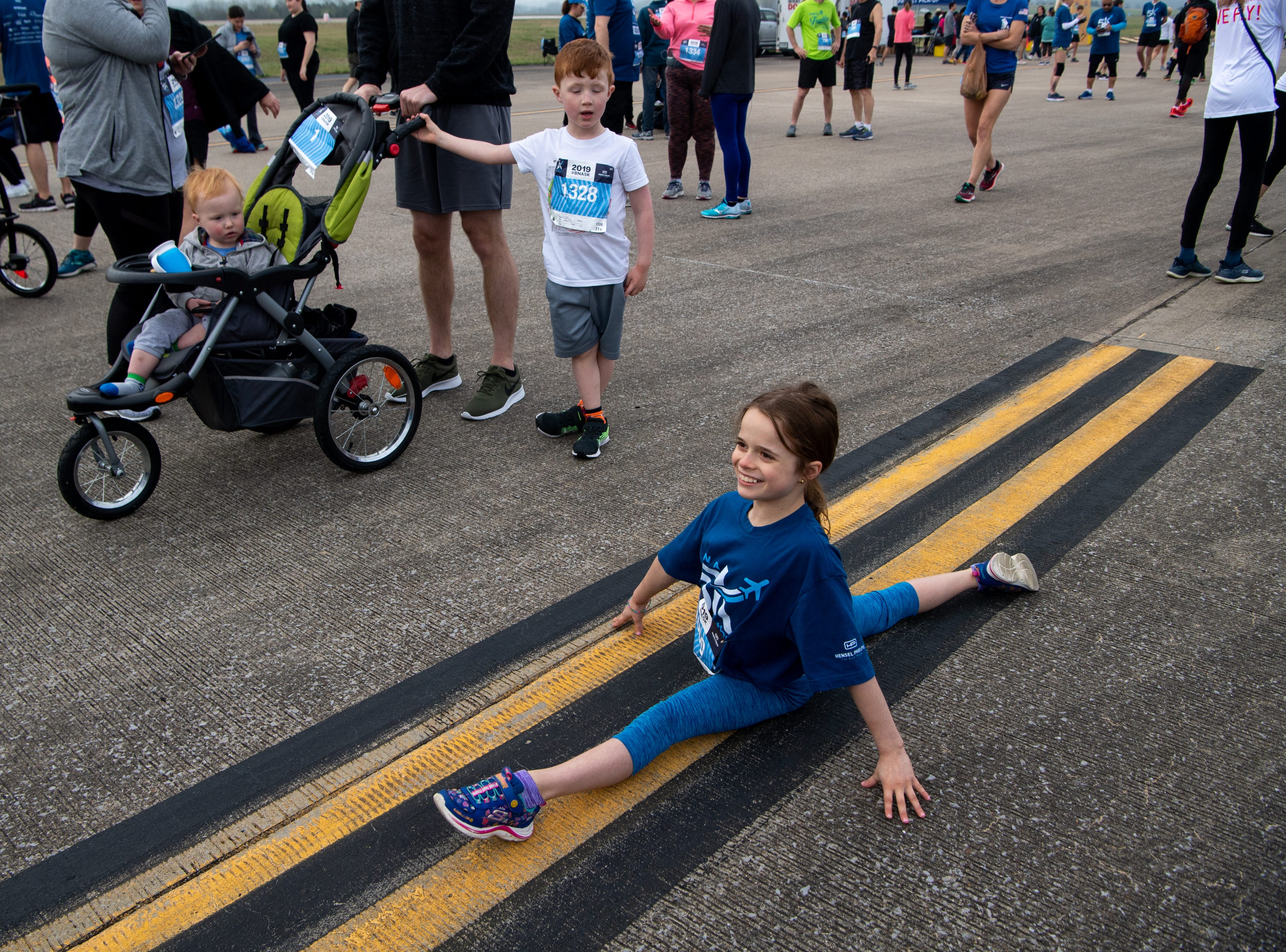 Ella Snyder, 9, stretches before the BNA 5K on the Runway at Nashville International Airport on Runway 2R/20L Saturday, April 6, 2019, in Nashville, Tenn.