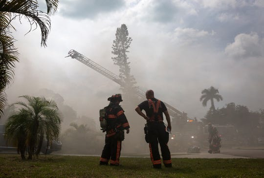 North Collier Fire and Rescue take a break as their crew members attempt to extinguish a house fire, Saturday, April 6, 2019, at the 800 block of 94th Avenue North in the Naples Park Community in North Naples.
